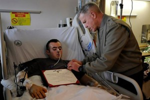 Gen. James Amos, commandant of the Marine Corps, pins on Cpl. Farrell Gilliams Purple Heart medal while the young Marine is in the Intensive Care Unit at Bethesda, Maryland Jan. 28, 2011.Courtesy photo