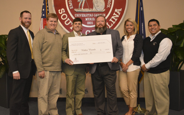 Pictured above left to right: Members of SVL Michael Bradbury (2015), Ryan Templeton (2014) and John Wall (2015) present a check to Hidden Wounds board members Freddie Brock, US Army (Ret.) and Steven Diaz, USMC (Ret.). Also pictured is Ashley Canara, a senior public relations student at USC and a volunteer with Hidden Wounds.